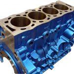 Blick schräg von oben auf einen 4-Zylinder Motorblock aus Stahl, so dass die Zylinderwände sichtbar sind