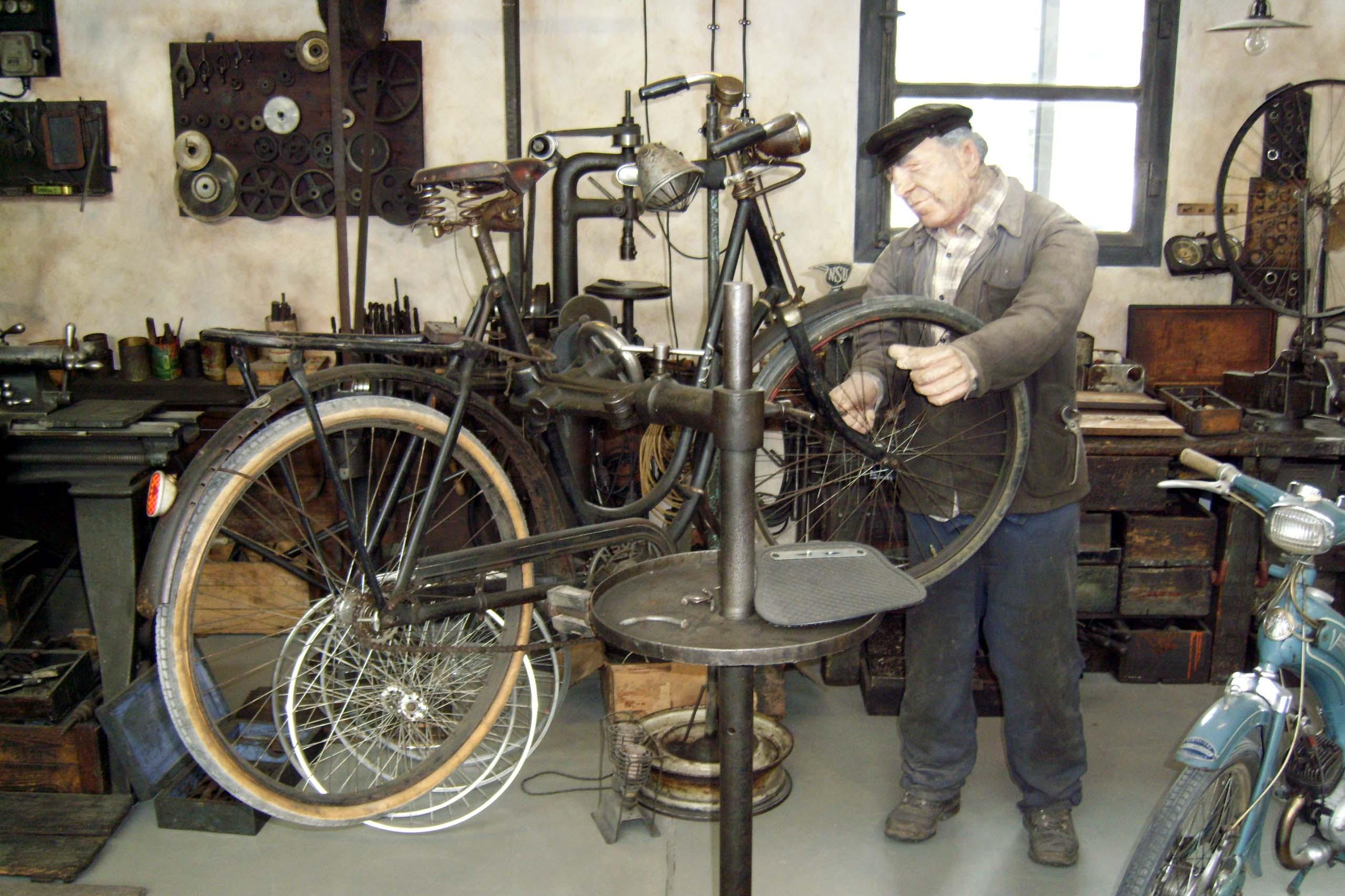 In dieser nostalgischen Zweiradwerkstatt werden gerade die Speichen eines Fahrrades kontrolliert