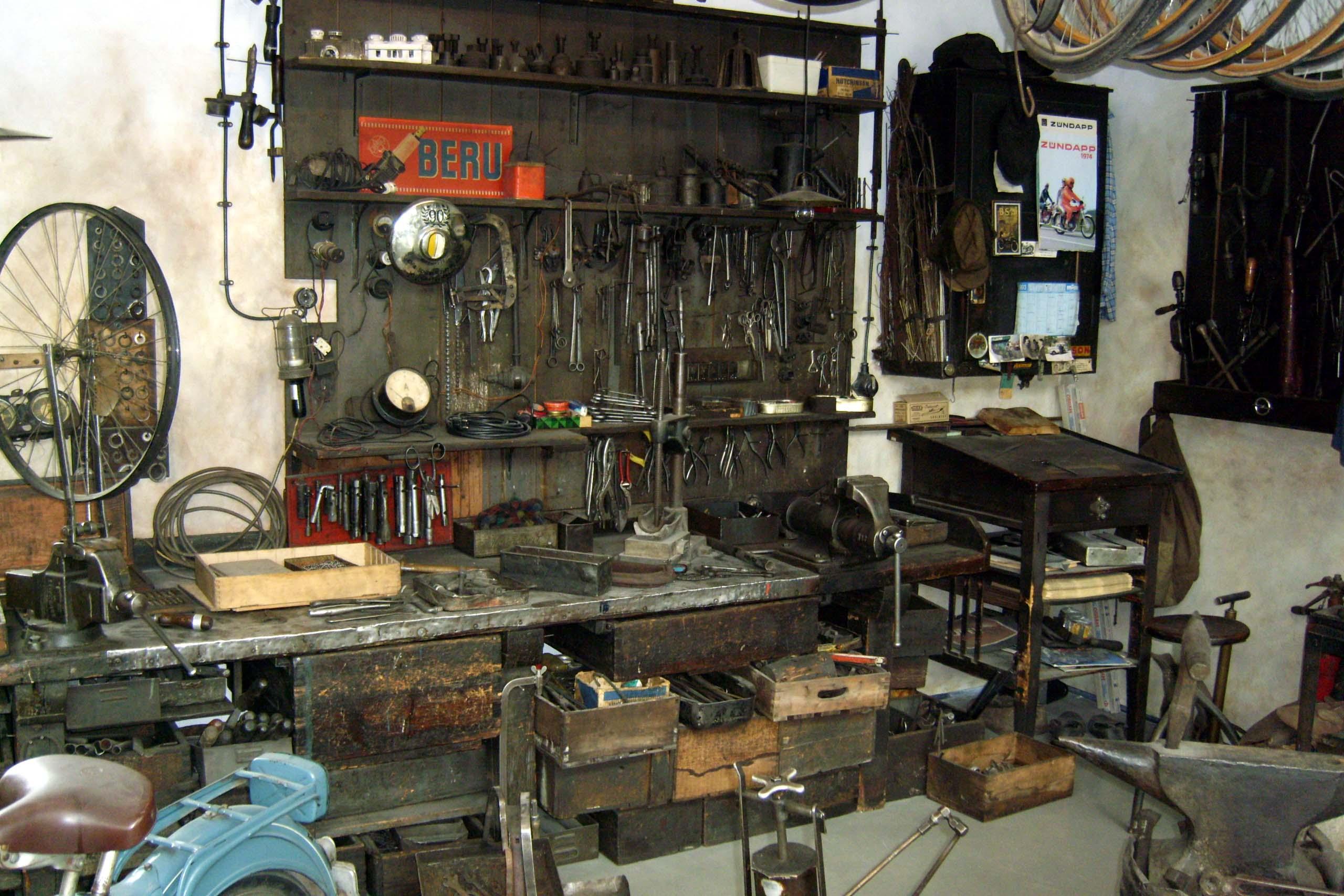 Blick in eine alte Zweiradwerkstatt mit Werkbank, Werkzeug und Ersatzteilen