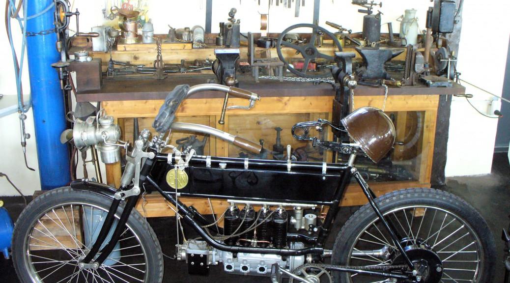 Blick in eine alte Zweiradwerkstatt mit einer besonderen Motorradkonstruktion im Vordergrund